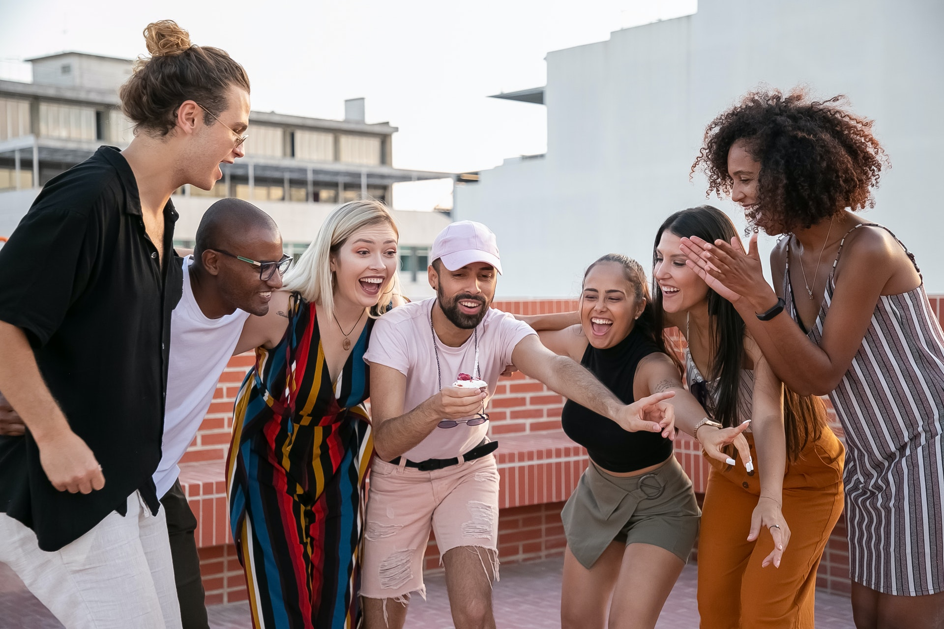 A group of friends standing on a roof top all gathered around anticipating doing something exciting