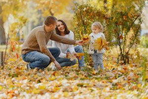Young couple squatting in leaves looking at each other and smiling while the man hands a leaf to a young daughter
