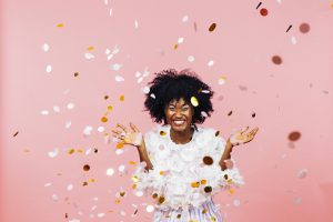 A Black woman in front of a pink background happy as confetti fills the air
